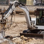 Excavator with hammer engaged in excavation of foundation